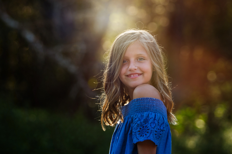 girl outdoors smiling at camera with sun glowing behind - atlanta family photographer